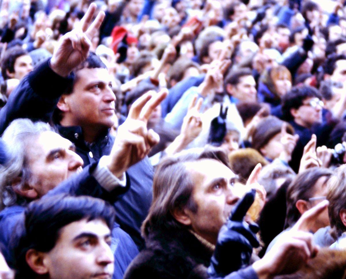写真・図版 : チェコの革命勝利を祝う30万人集会の間中、6歳の息子を肩車していたバイオリンの演奏家は「この光景を息子の目に生涯焼き付かせたかったから」と語った=1989年12月10日、プラハ、筆者撮影
