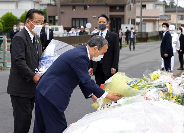 事故現場の献花台に花を手向ける菅義偉首相(手前)。左は八街市の北村新司市長=2021年7月1日午後2時8分、千葉県八街市、代表撮影 2021年7月1日