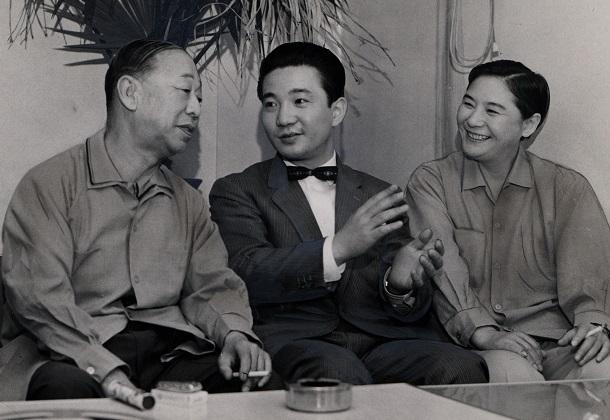 写真・図版 : NHK『ジェスチャー』の司会者・小川宏アナ(中央)をはさんで話をする柳家金語楼(左)と水の江瀧子=1961年