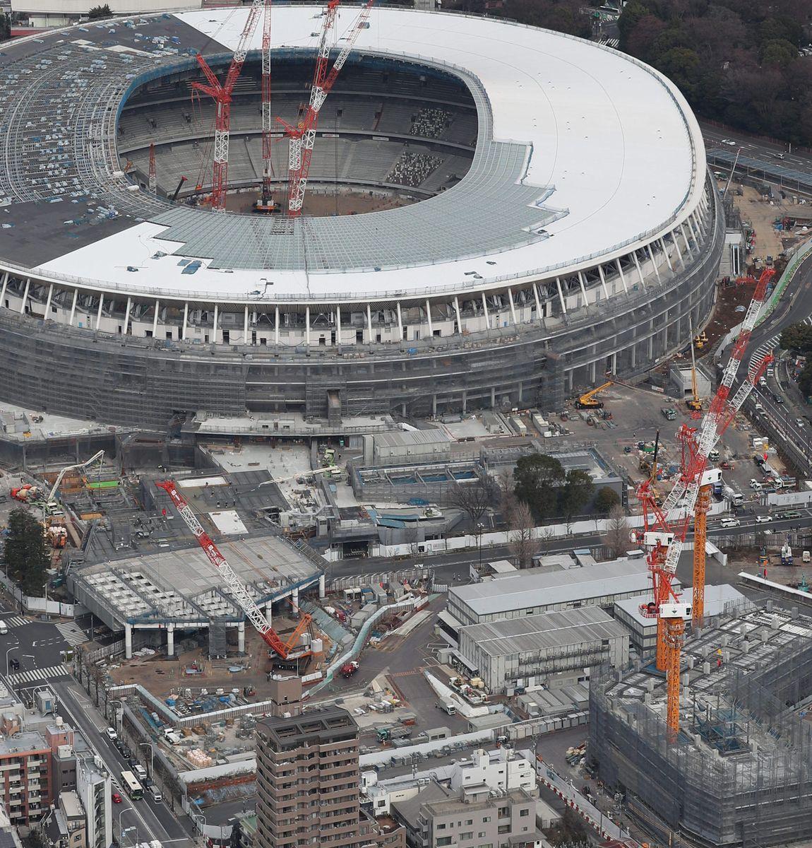 写真・図版 : 新国立競技場の建設当時の様子。南側にあった都営霞ケ丘アパートの跡地では歩行デッキが工事中。一帯は公園となった=2019年2月