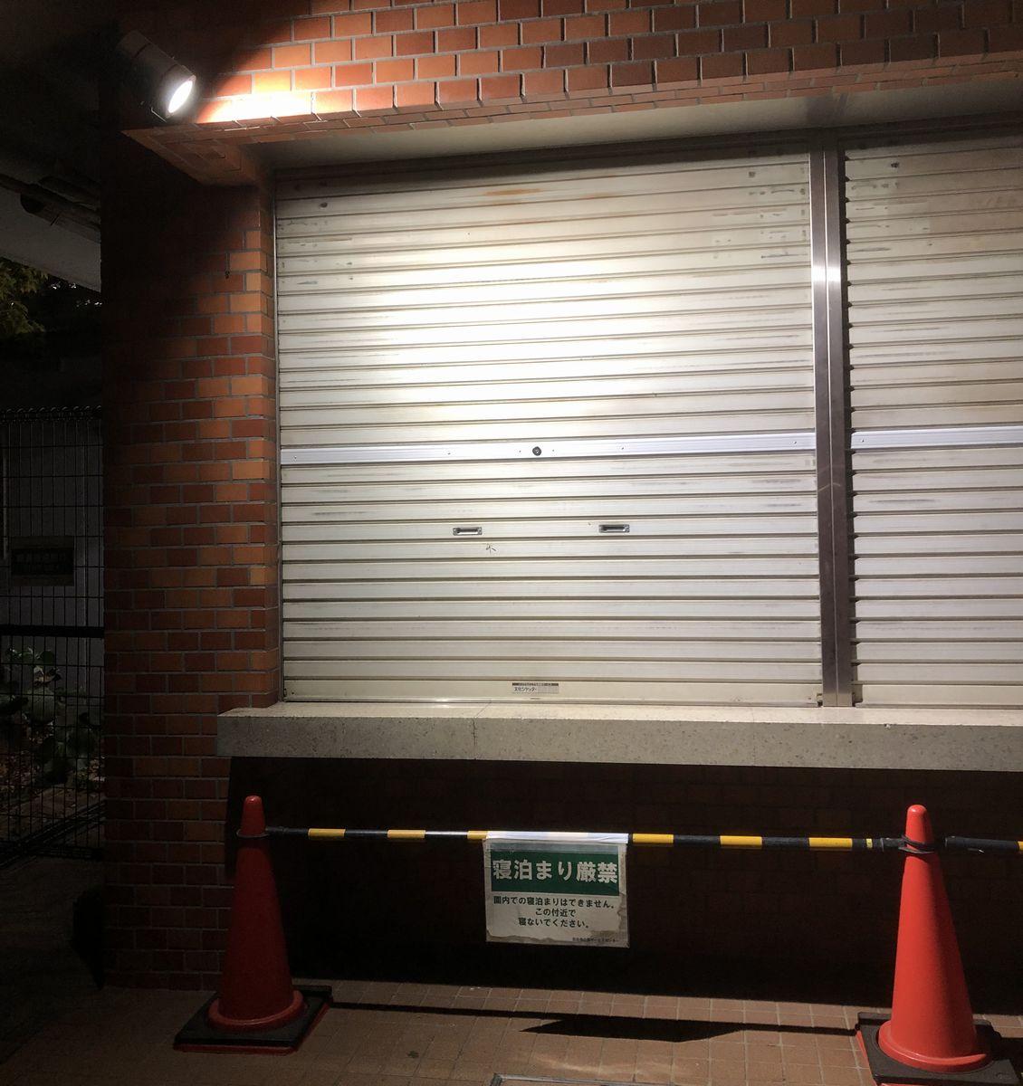 写真・図版 : 東京・日比谷公園に取り付けられた照明。「寝泊まり厳禁」の警告板も設置されている=2021年4月19日