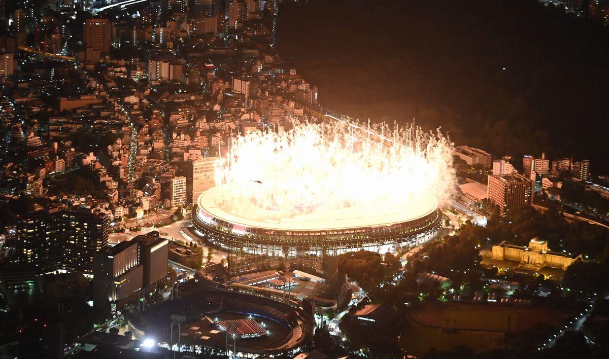 写真・図版 : 無観客で開かれた東京五輪の開会式。花火が緊急事態宣言下の東京の街を照らした=2021年7月23日午後11時49分、東京・国立競技場、朝日新聞社ヘリから