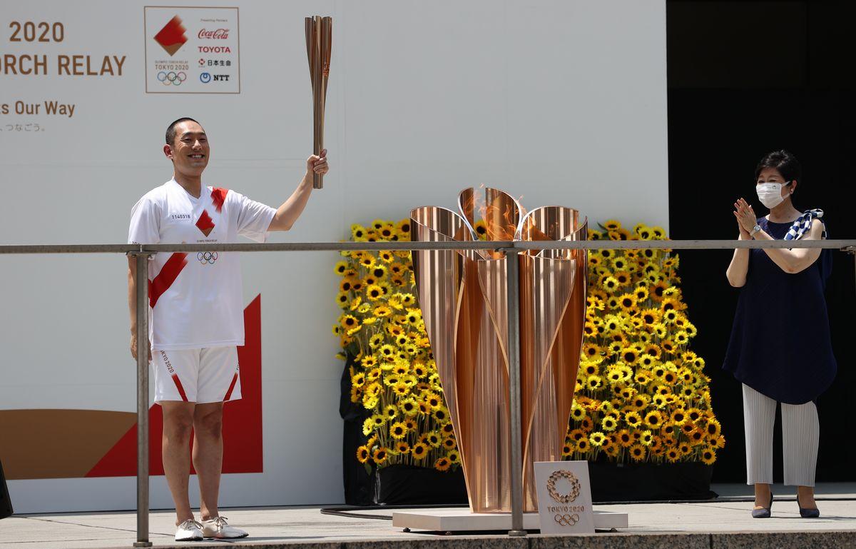 写真・図版 : 聖火リレー到着式で、聖火台に火をともした歌舞伎俳優の中村勘九郎さん(左)。右は東京都の小池百合子知事=2021年7月23日午後、東京都新宿区