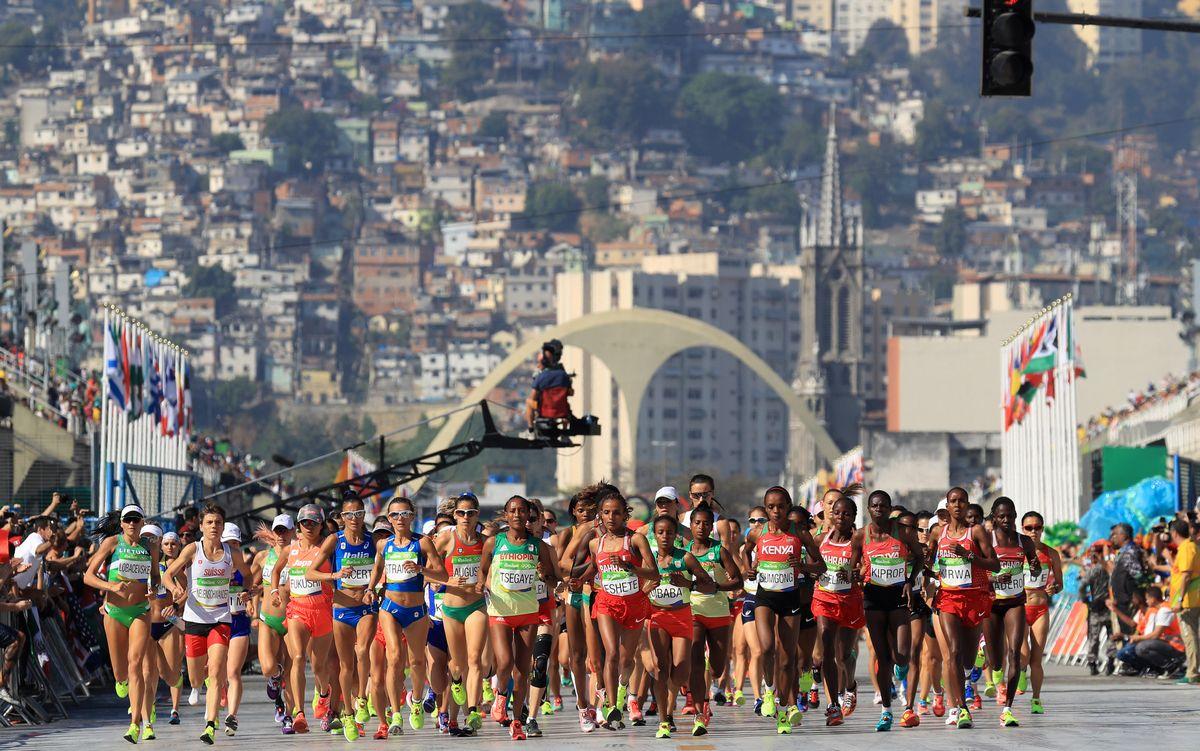 写真・図版 : リオ五輪の女子マラソンで、ファベーラを背にスタートする選手たち=2016年8月14日