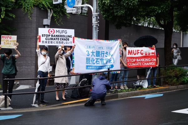 写真・図版 : MUFGの株主総会の会場前で株主に提案への賛同を訴えるNGOのメンバーら=2021年6月29日、東京都内、350.org Japan提供