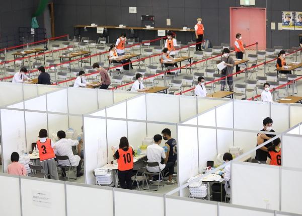 写真・図版 : 広島大学の体育館で新型コロナウイルスワクチンの接種を受ける学生ら=2021年6月21日、広島県東広島市