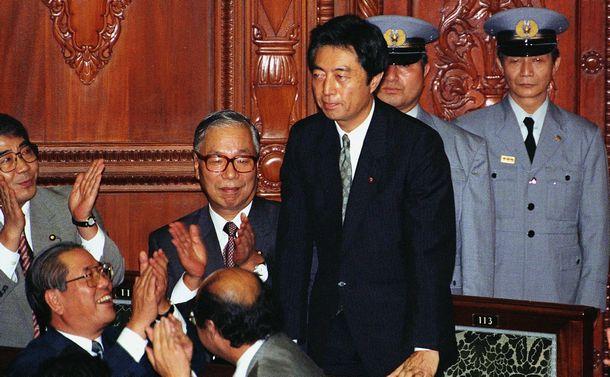 写真・図版 : 衆議院本会議で首相に指名され、立ち上がって議員の祝福にこたえる細川護煕・日本新党代表。左は武村正義・新党さきがけ代表 =1993年8月6日