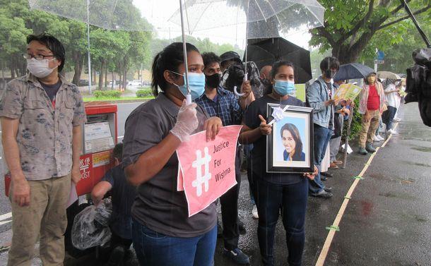 写真・図版 : 宮島ヨハナさんが呼びかけたスタンディングに参加した、ウィシュマ・サンダマリさんの2人の妹。ウィシュマさんの遺影と、#JusticeForWishmaというハッシュタグを掲げている=2021年7月30日、東京・霞が関の法務省前
