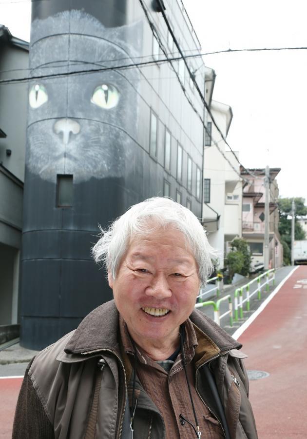 写真・図版 : 「猫ビル」の前で写真に収まる立花隆さん=2016年3月、東京都文京区