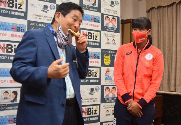 河村たかし・名古屋市長(左)が、東京五輪ソフトボールの金メダルを突然かじった。手渡した後藤希友投手は一瞬驚いた顔をみせた=2021年8月4日午前10時1分、名古屋市役所