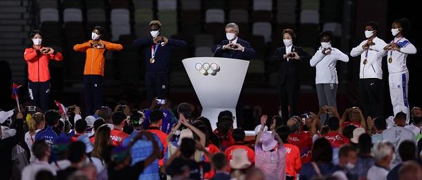 写真・図版 : 東京五輪の閉会式でハートマークを作るIOC(国際オリンピック委員会)のトーマス・バッハ会長(中央)と6人のアスリート(阿部詩選手は一番左)、橋本聖子組織委員会会長(バッハ氏の向かって右隣)=2021年8月8日