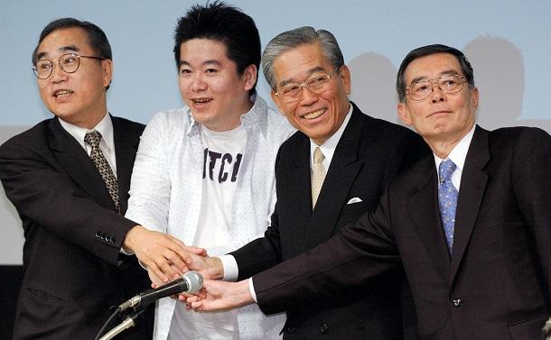写真・図版 : ライブドアとフジテレビジョンは、資本・業務提携に合意し和解したことを正式発表したが・・・。記者会見後、報道陣の求めに応じ握手する(左から)亀渕ニッポン放送社長、堀江ライブドア社長、日枝フジテレビ会長、村上・同社長(肩書はいずれも当時)=2005年4月18日、東京都港区台場