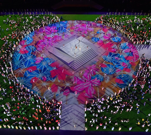 写真・図版 : 東京五輪閉会式・パフォーマンス(中央)を見る選手たち=2021年8月8日、東京・国立競技場