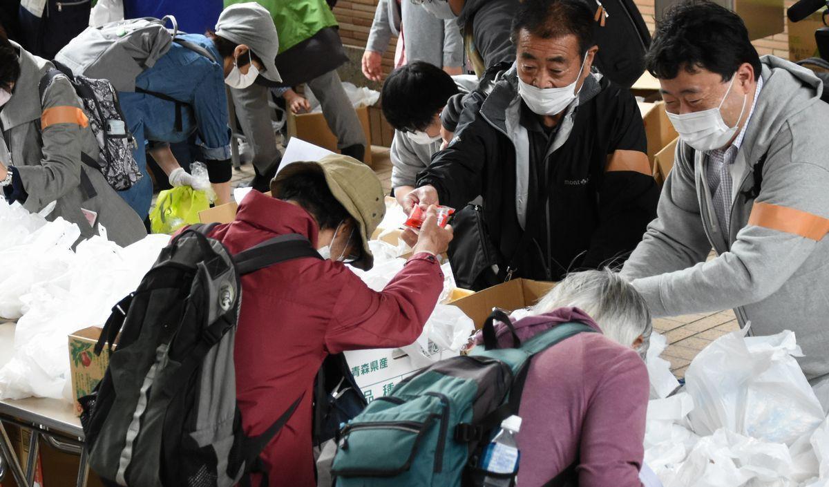 写真・図版 : 食料配布や相談会を無償で行う「ゴールデンウィーク大人食堂」でスタッフから食料を受け取る人たち。コロナ禍で生活困窮者が増え厳しさも増す一方で、生活保護制度への忌避意識は根強い問題だ=2021年5月5日、東京都千代田区