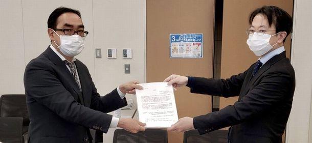 写真・図版 : 生活保護に関する広報の強化やオンライン申請の導入を求めて、厚生労働省へ申し入れた(右は筆者)=2020年12月
