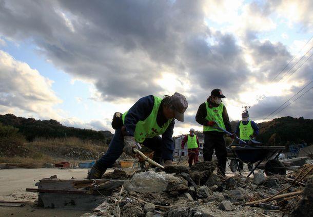 写真・図版 : 東日本大震災で被災した岩手県釜石市で、ボランティアが解体された家屋のがれきを片付ける。石川県野々市市から来た村中外志明さん(53)は「寒くなるにつれ、屋外の作業はつらくなる。でも、活動している様子を見て、被災地の人たちが元気になってくれたら」と話した=2011年12月2日