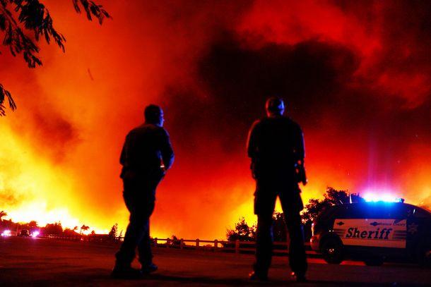 写真・図版 : ロサンゼルスの北西で起きた山火事で、警備する警察官=2018年11月9日、カリフォルニア州シミバレー