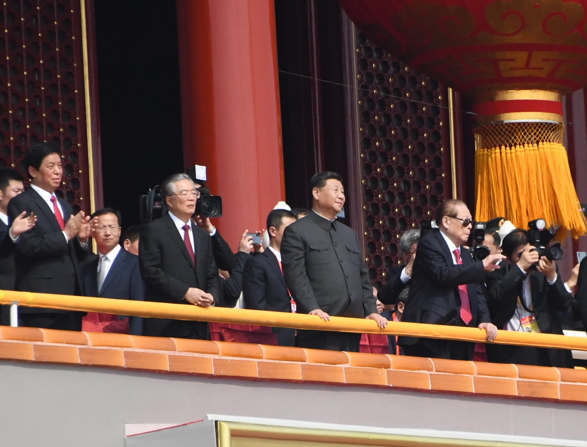 写真・図版 : 中国建国70年祝賀式典で、軍事パレードを見守る習近平氏。右は江沢民氏(2019年、天安門で)
