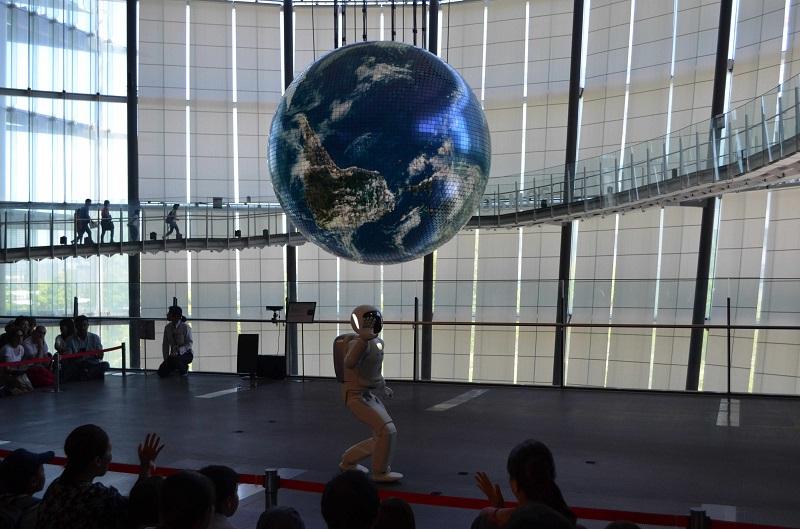 写真・図版 : 科学未来館を象徴する大型の地球ディスプレー「ジオ・コスモス」のあるシンボルゾーンで実演してみせるロボット「アシモ」=2018年6月