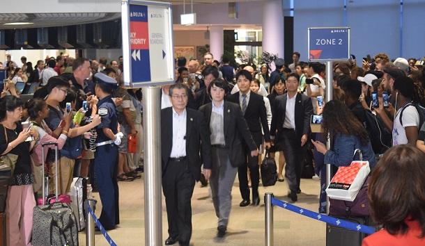 写真・図版 : 米国に向け、搭乗口に向かう小室圭さん(中央)=2018年8月7日、成田空港
