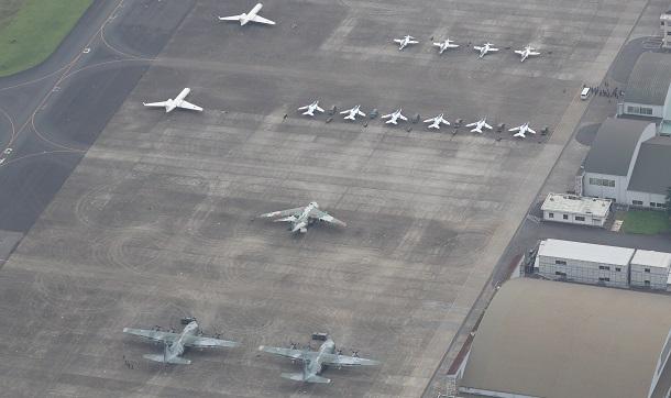 写真・図版 : 都心を飛行する前のブルーインパルス(右上)。一番手前の2機は、アフガニスタンに残る日本人らを退避させるため準備するC130輸送機=2021年8月24日、埼玉県狭山市の航空自衛隊入間基地