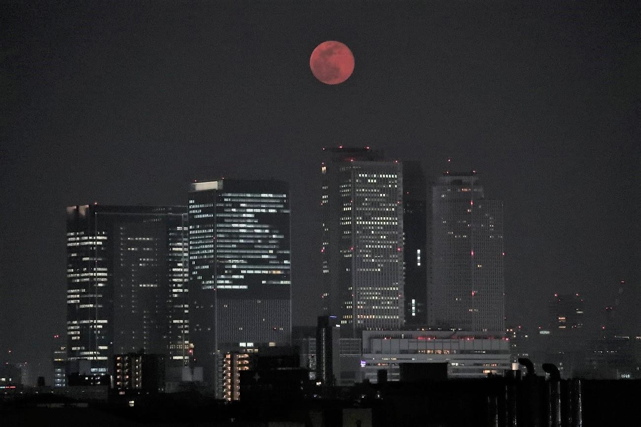 写真・図版 : 名古屋駅前の高層ビル群の上に浮かんだスーパームーン=2020年4月8日