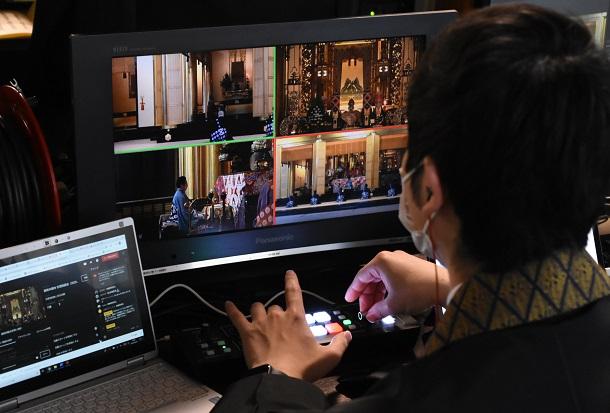 写真・図版 : 機器を操作し、法要をネット中継する僧侶=2020年5月、東京都中央区
