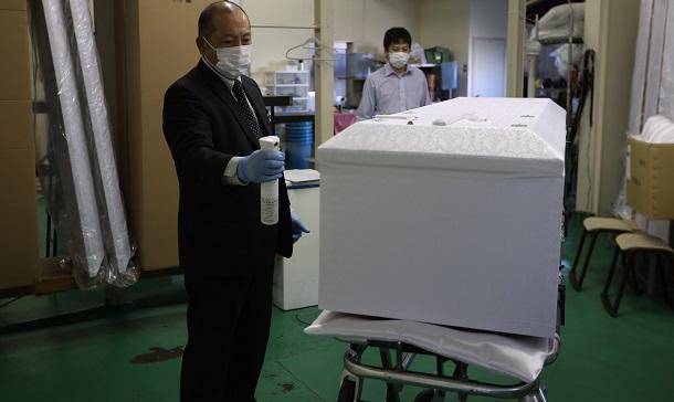 写真・図版 : 新型コロナウイルスの感染が疑われる遺体の入った棺を冷蔵安置室から出し、消毒する葬儀会社の従業員=2020年5月、東京都板橋区