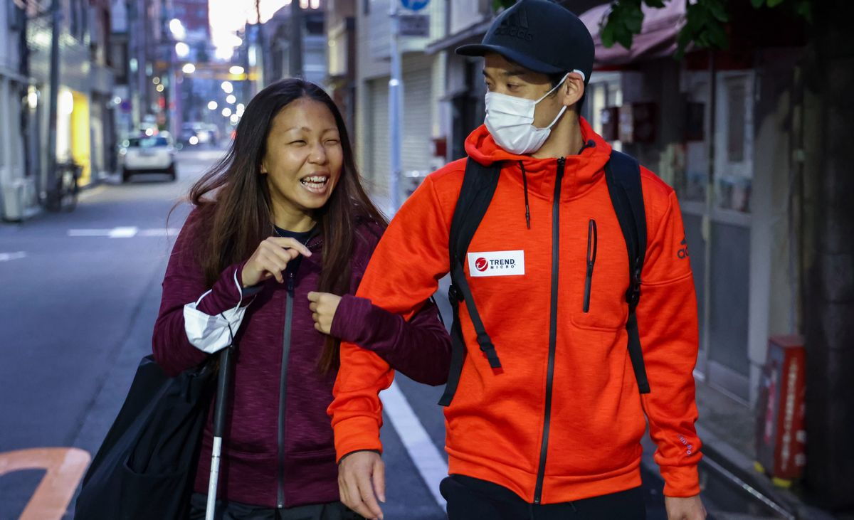 写真・図版 : 白杖を持つ高田千明さんの腕を夫の裕士さんが取って歩く。裕士さんは聴覚障害者のオリンピック「デフリンピック」日本代表で専門は400㍍ハードル。千明さんは口の動きを見て会話する裕士さんのため、マスクを外していた=2020年11月26日、東京都台東区