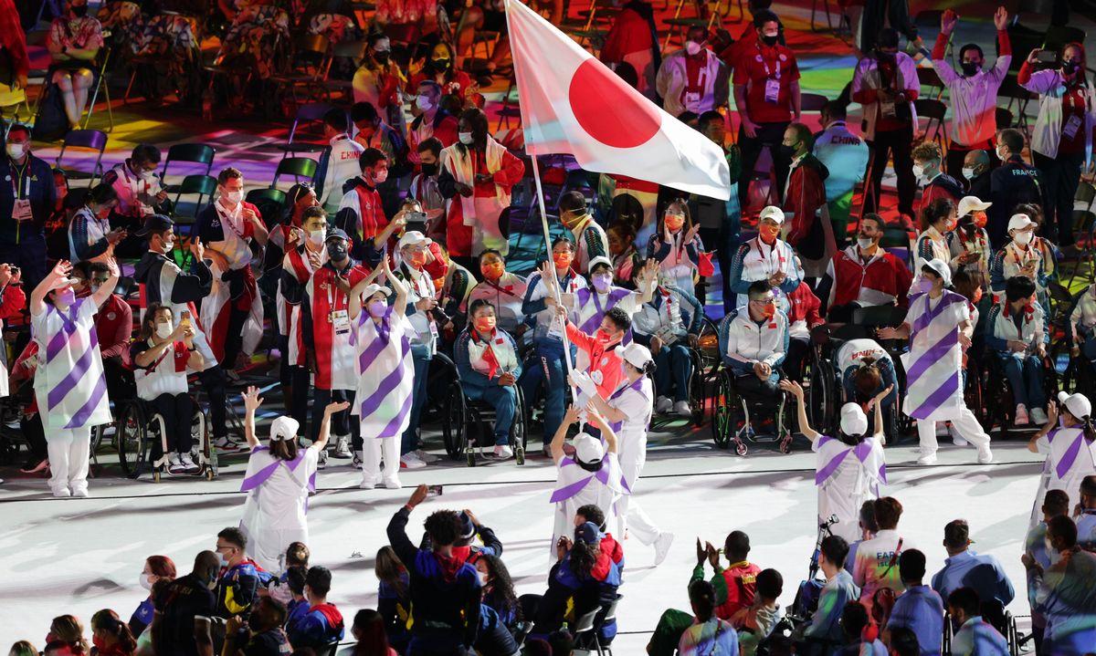 写真・図版 : 各国・地域の選手たちが見守るなか、日の丸を手に入場する卓球の岩渕幸洋選手と日本選手団=2021年9月5日、国立競技場
