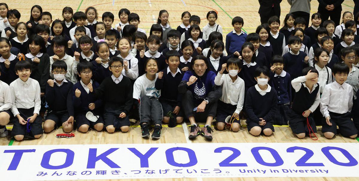 写真・図版 : 東京パラリンピックに向けた体験授業で、有明西学園の児童と記念写真を撮る高田千明選手(中央左)と大森盛一さん(同右)=2020年2月25日、東京都江東区