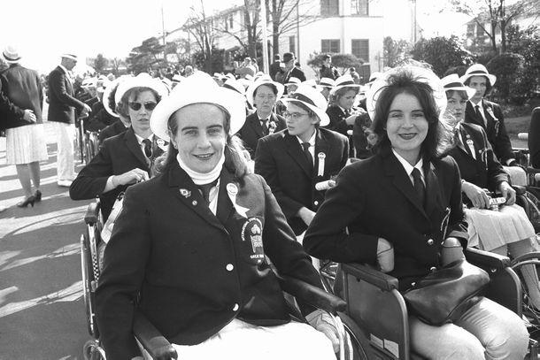 写真・図版 : 国際身体障害者スポーツ大会東京大会(パラリンピック東京大会)第一部国際大会の開会式が1964年11月8日、東京・代々木選手村の織田フィールドで開かれた。写真は、にこやかに開会式を迎えたイギリスの女子選手たち