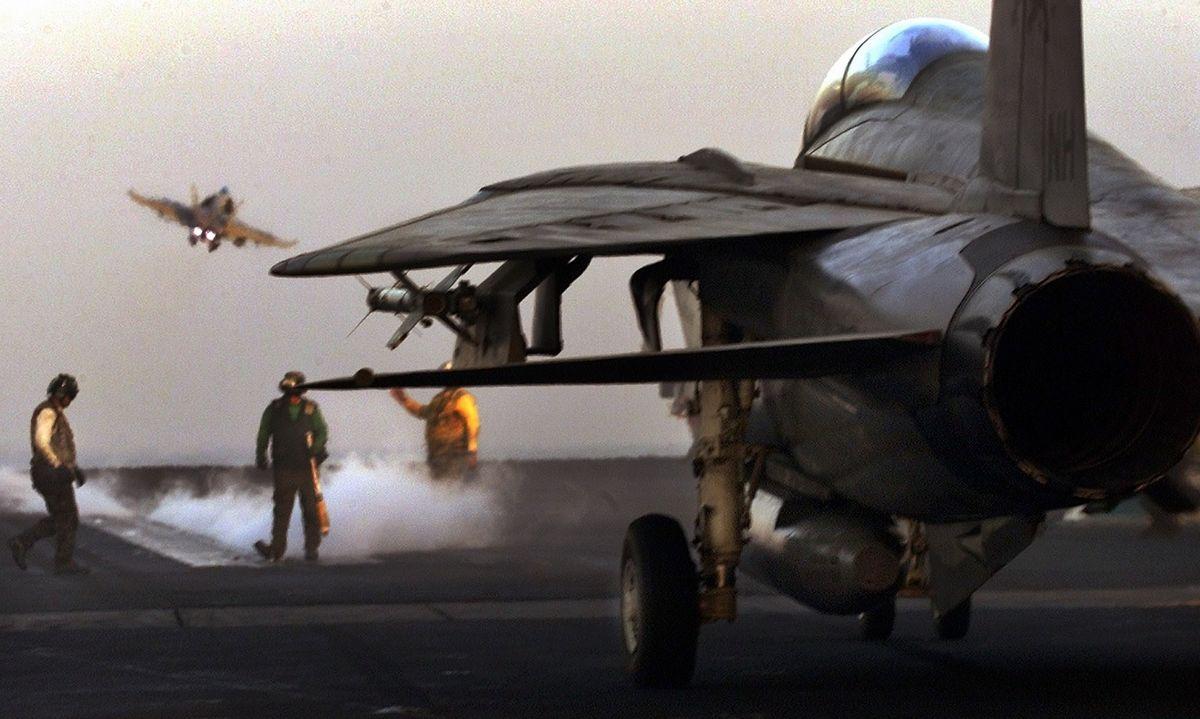 写真・図版 : アフガニスタン攻撃のため米空母から出撃する戦闘攻撃機=2001年11月、アラビア海