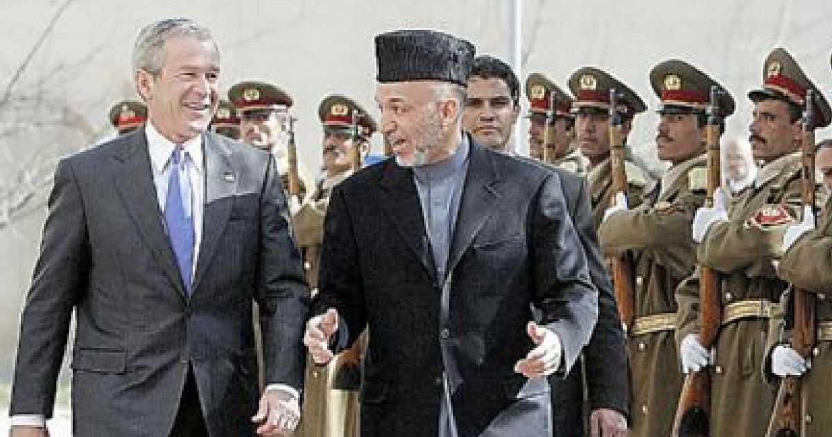 写真・図版 : カブールでアフガニスタンのカルザイ大統領と並んで歩くブッシュ米大統領。ブッシュ氏は01年の同時多発テロを受けてアフガニスタン攻撃を始め、当時のタリバン政権を崩壊させた=2006年3月1日