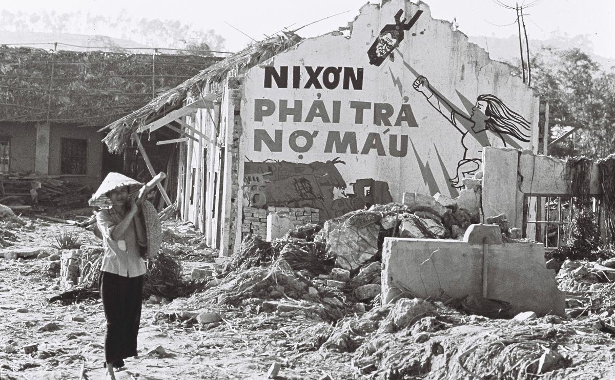 写真・図版 : 北ベトナム・ハイフォン省は1972年4月16日の北爆再開から10月30日までに44の市街地、198の部落が爆撃され、2000人以上が死傷した。写真はハイフォン市郊外のケン・アン地区の民家。壁に「ニクソンよ、われわれの血を返せ」と書いてある=1972年11月