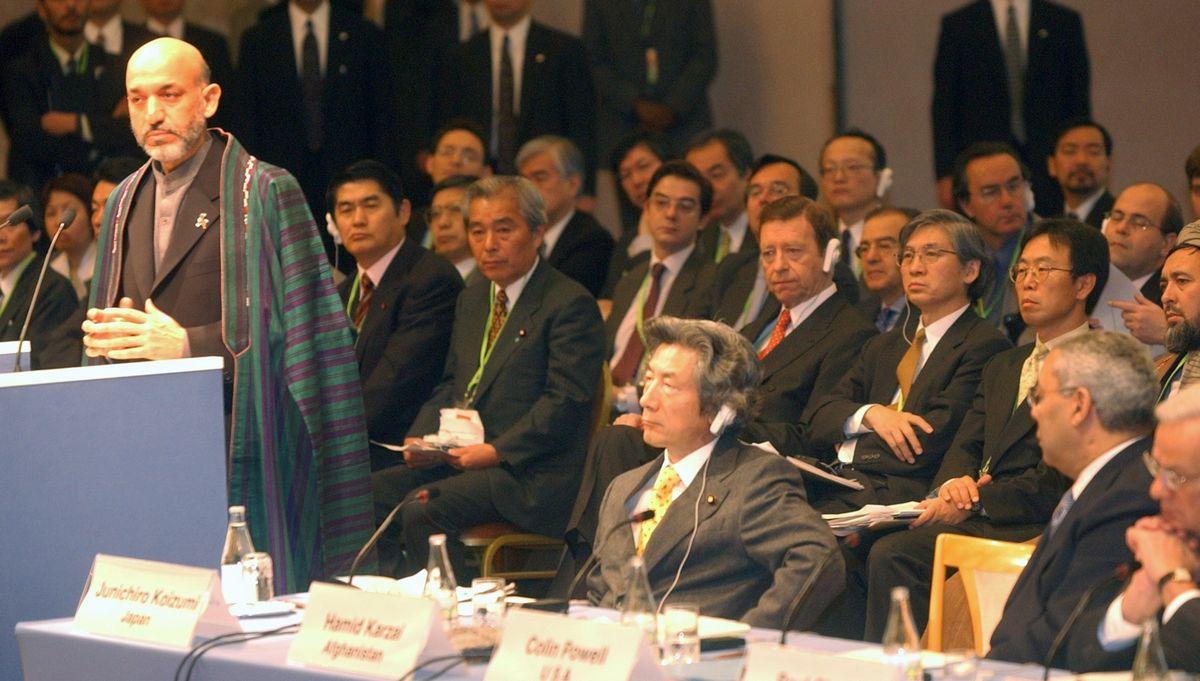 写真・図版 : アフガニスタン復興支援国際会議で演説するアフガニスタン暫定政権のカルザイ議長。右隣は小泉純一郎首相、パウエル米国務長官=2002年1月21日、東京都港区