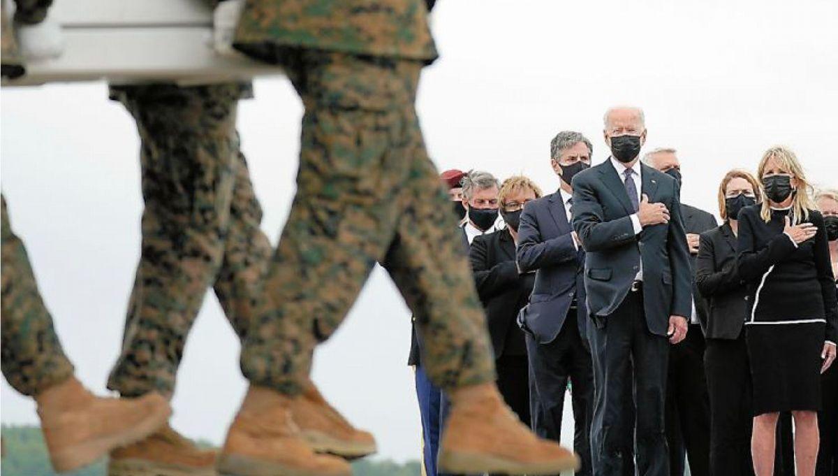 写真・図版 : アフガニスタンでの爆破テロ事件で亡くなった米兵のひつぎを出迎えたバイデン大統領ら=2021年8月29日、米デラウェア州のドーバー空軍基地