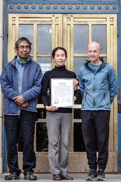 アラスカ州議会の表彰状を手に友人らと州議会前に立つ星野直子さん