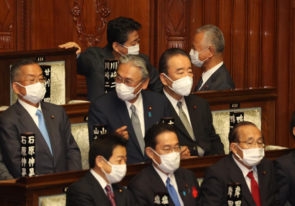 衆院本会議での首班指名選挙中、会話を交わす甘利氏(奥右)と安倍元首相(奥左)
