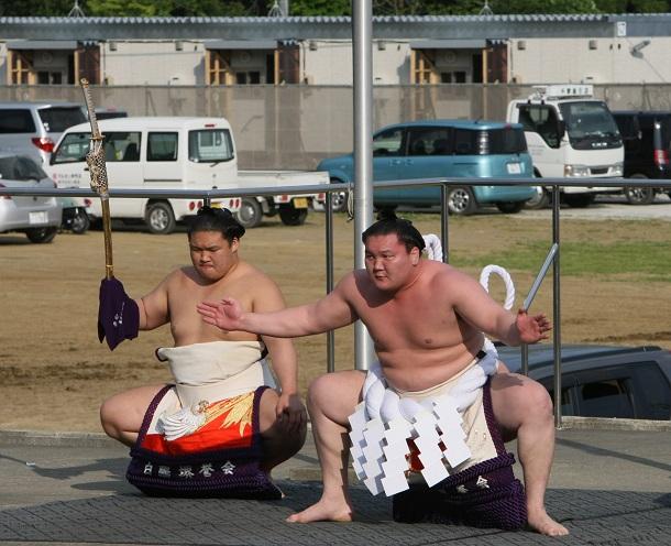 避難所になっている志津川中で土俵入りする横綱・白鵬。後方に仮設住宅が並ぶ=6日午後4時32分、201106