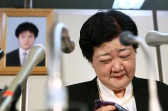 写真・図版 : 亡くなった上嶋浩幸さんの遺影を背に、会見で涙をぬぐう母親の幸子さん=11日午後5時27分、東京・霞が関の司法記者クラブ、細川卓撮影