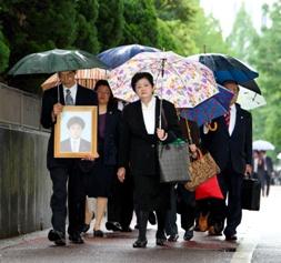写真・図版 : 亡くなった上嶋浩幸さんの遺影を抱えて東京地裁に入る父正人さん(手前左)と母幸子さん(同右)=11日午後1時3分、東京・霞が関、細川卓撮影