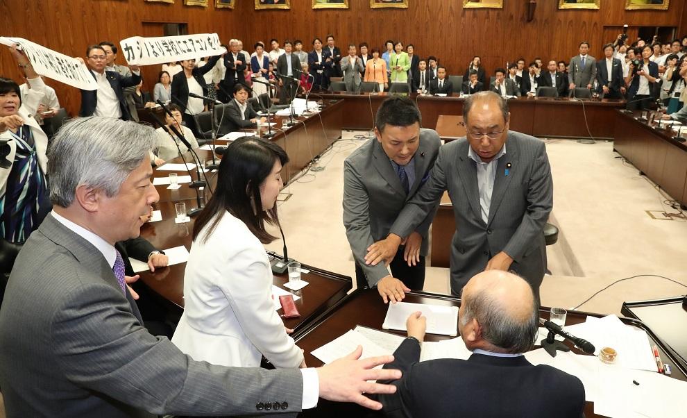 写真・図版 : 参院内閣委で、カジノを含む統合型リゾート(IR)実施法案の採決があり、野党の議員が委員長席に詰め寄った=2018年7月19日午後4時41分、岩下毅撮影