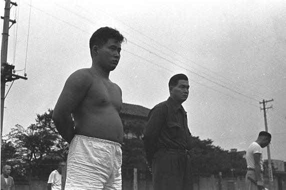 写真・図版 : 右翼団体「殉国青年隊」隊員のけいこを見守る豊田一夫隊長(左)=1953年、東京都品川区滝王子町