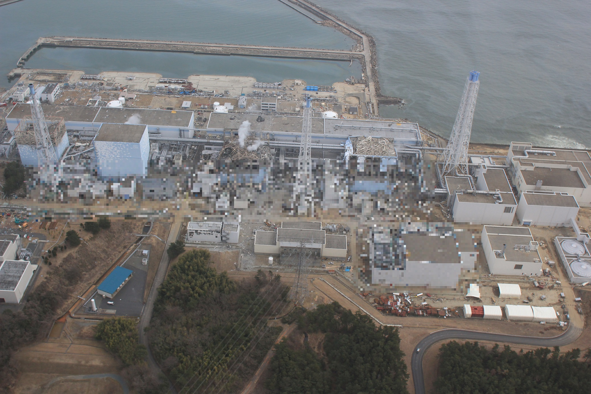 写真・図版 : 共用プール建屋(右手前)と1~4号機(奥)。共用プール建屋1階には2、4号機用の非常用ディーゼル発電機が1台ずつ設置されていた=東京電力ホールディングスが2020年12月22日に公表した2011年3月20日撮影の「福島第一原子力発電所事故の状況に係る写真」